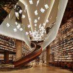 Una librería china con hojas de papel iluminadas flotando en el aire