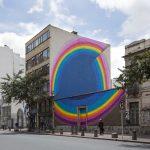 Artista callejero crea murales con diseños de arco iris